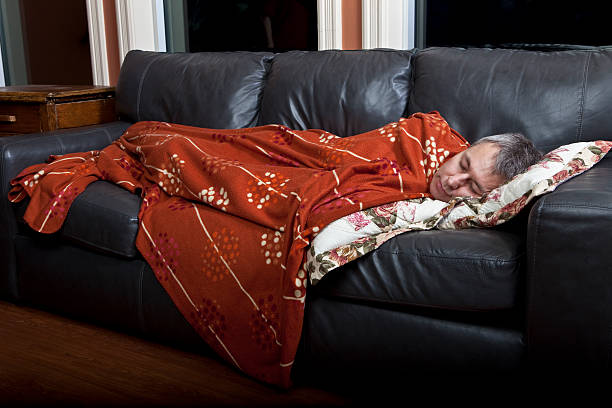 Man sleeping on the couch stock photo