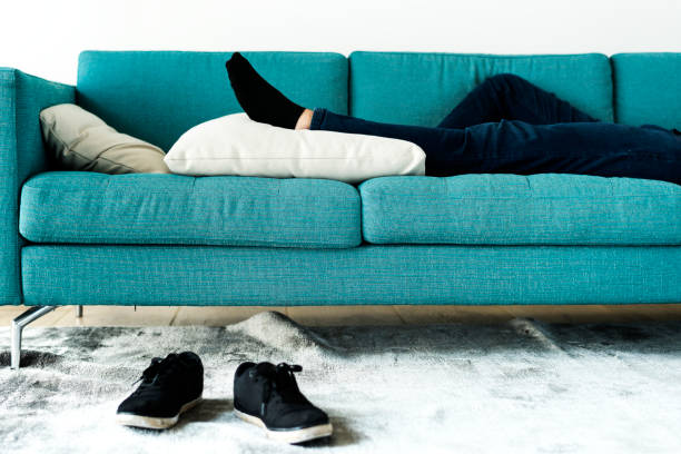 man sleeping on the sofa - sloth stock pictures, royalty-free photos & images