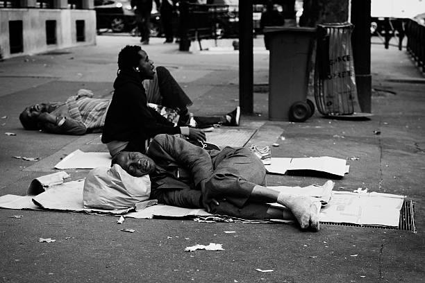 man sleeping on the street in paris - bettler stock-fotos und bilder