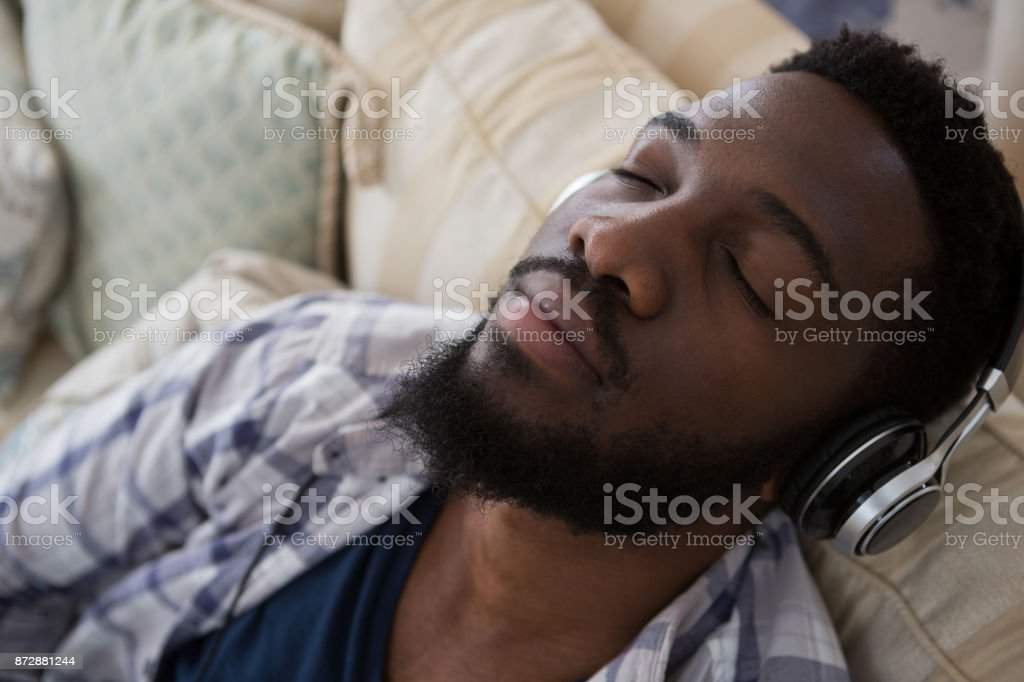 Man Sleeping While Listening To Music Stock Photo - Download Image Now