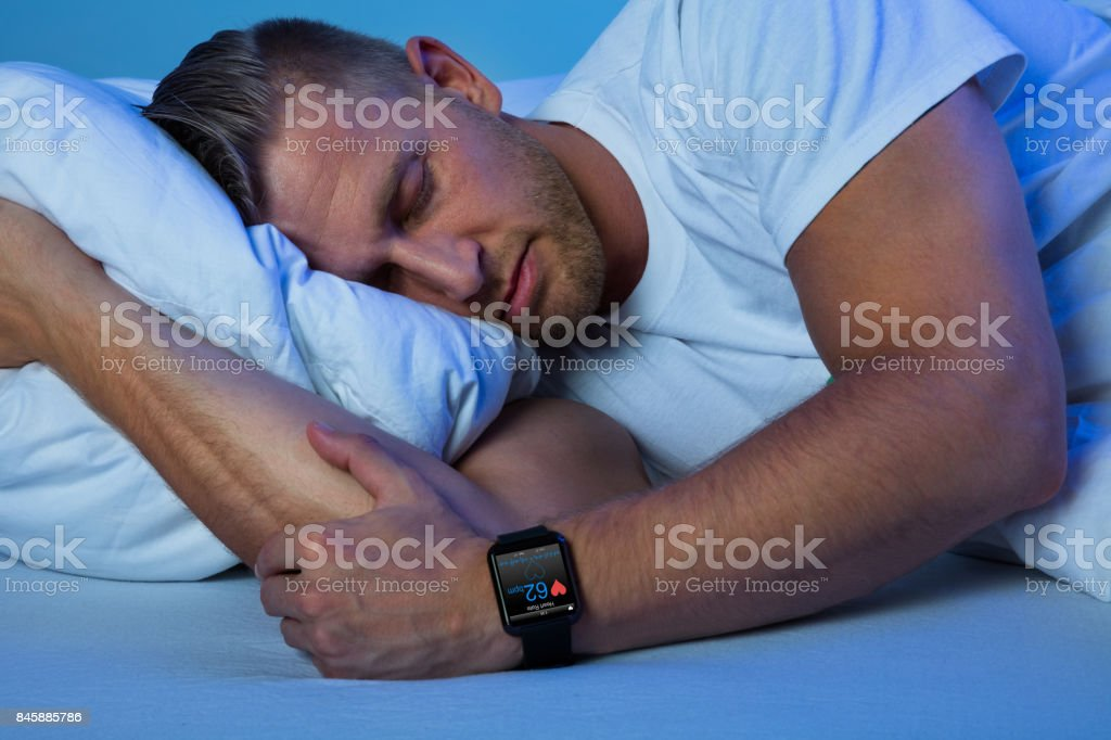 Man Sleeping With Smart Watch In His Hand stock photo