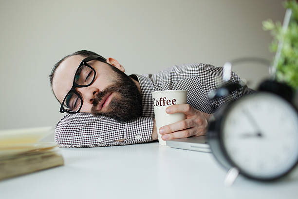 Man sleeps on office table over laptop with coffee stock photo