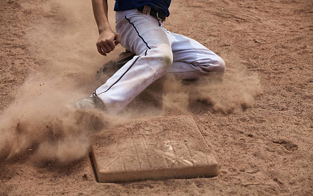 A man sliding into the base while playing ball stock photo