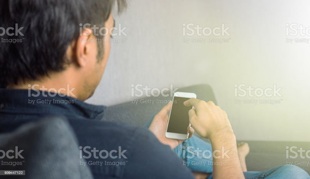 Man sliding phone, sitting on sofa at home stock photo