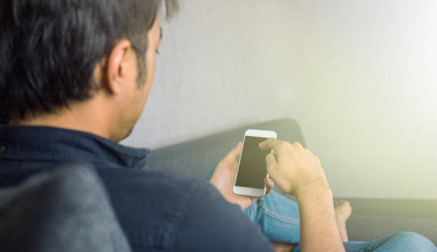 man sliding phone, sitting on sofa at home - asian with phone house background stock photos and pictures