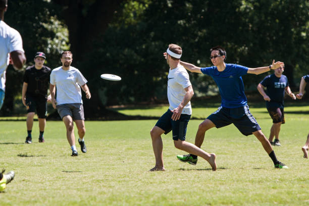 Man Slings Disc To Teammate In Atlanta Ultimate Frisbee Game Atlanta, GA, USA - July 28, 2018:  A man tosses a frisbee to a teammate in an ultimate frisbee game in Piedmont Park on July 28, 2018 in Atlanta, GA. plastic disc stock pictures, royalty-free photos & images