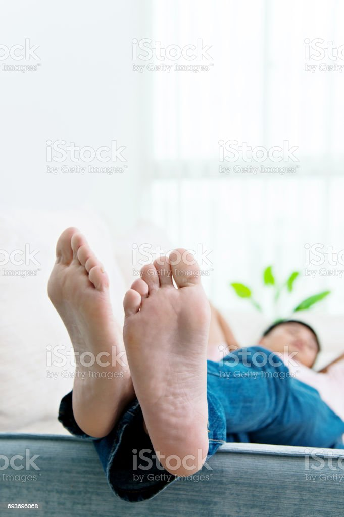 Man slipping on the sofa with feet up stock photo