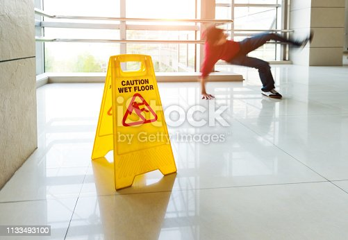 Man slips falling on wet floor next to the wet floor caution sign.