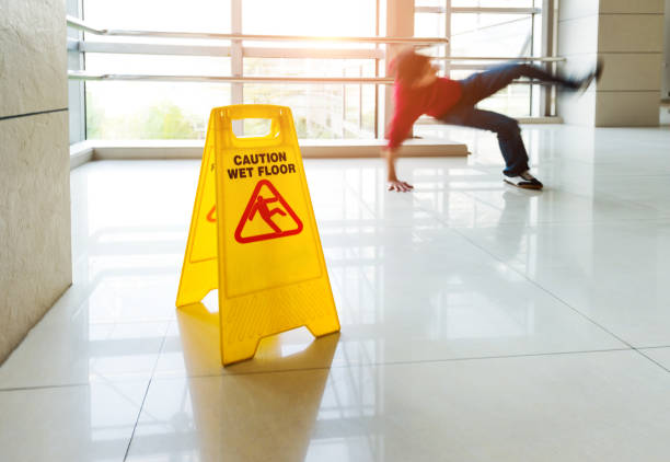 Man slips falling on wet floor Man slips falling on wet floor next to the wet floor caution sign. falling stock pictures, royalty-free photos & images