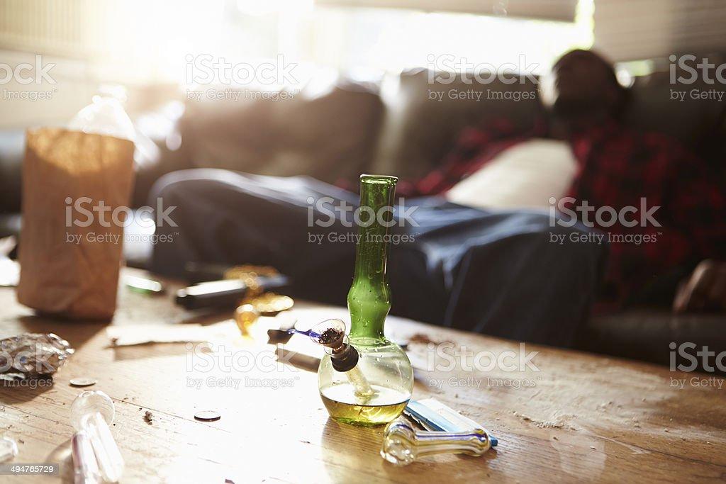 Man Slumped On Sofa With Drug Paraphernalia In Foreground stock photo