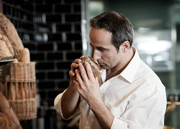 Man smelling at bread in supermarket stock photo