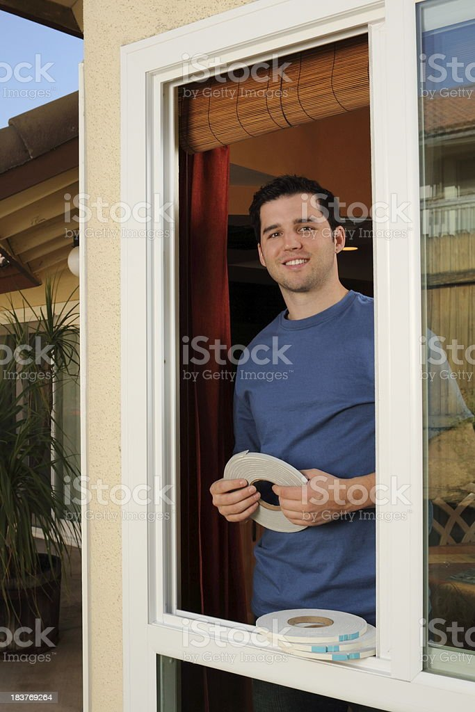 Man Smiles Before Installing Weather Stripping stock photo