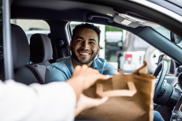 Man smiles while picking up curbside order stock photo