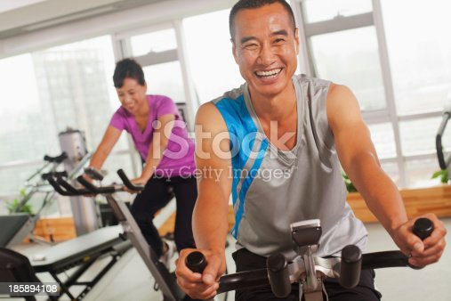 istock Man smiling and exercising on the exercise bike 185894108