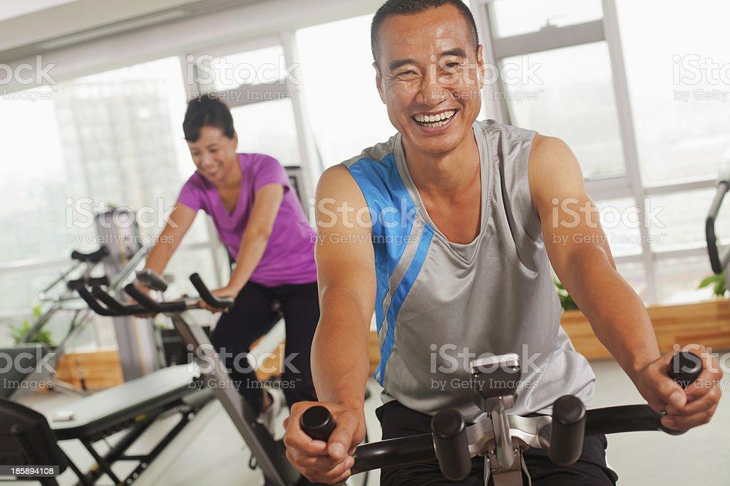 Hombre sonriendo y ejercicio en la bicicleta de ejercicio - foto de stock