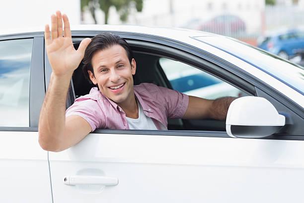 homme souriant et agiter les mains - homme faire coucou voiture photos et images de collection