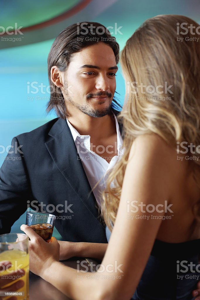 Man smiling at woman with glass in hand royalty-free stock photo
