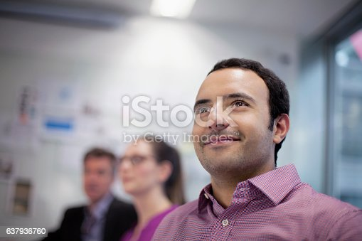 istock Man smiling in design studio planning presentation with coworkers 637936760