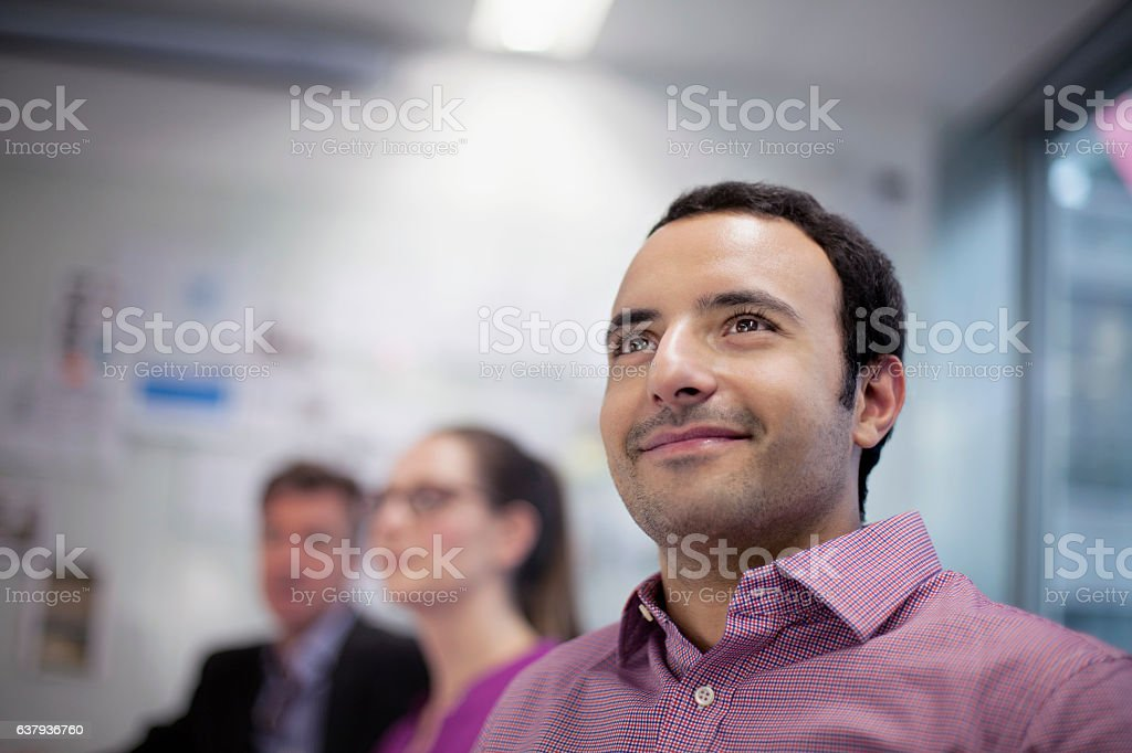 Man smiling in design studio planning presentation with coworkers stock photo