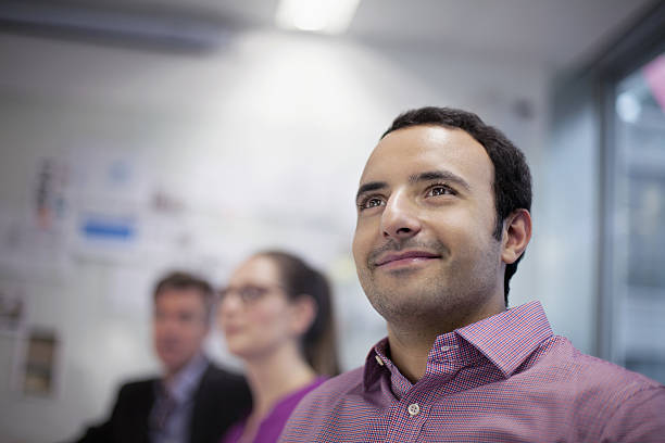 Man smiling in design studio planning presentation with coworkers Man smiling in design studio planning presentation with coworkers bending over backwards stock pictures, royalty-free photos & images