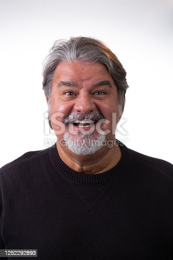 Studio portrait of a man in his 50s. He is smiling and looking to the camera. He has beard and gray hair.