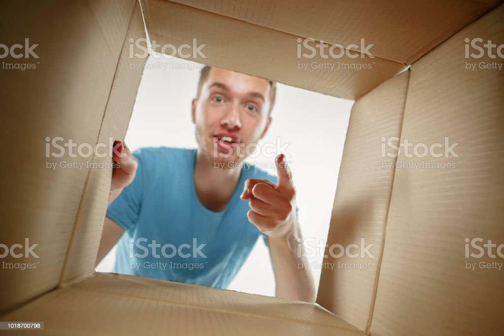 Man smiling, opening box and looking inside. The package, delivery,...