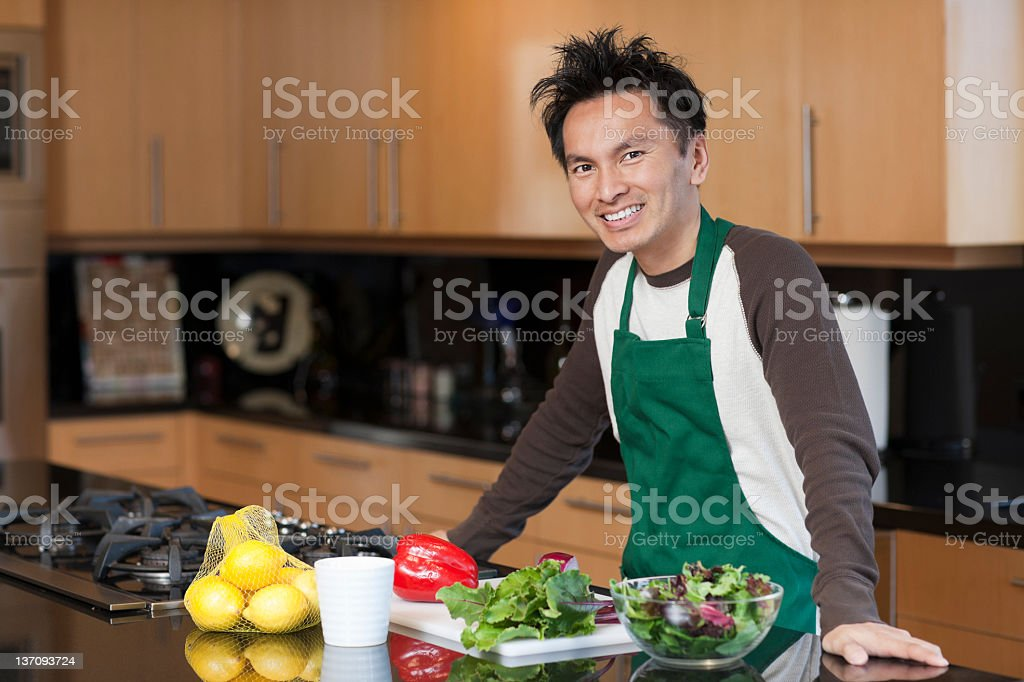 Man smiling, wearing apron in kitchen royalty-free stock photo