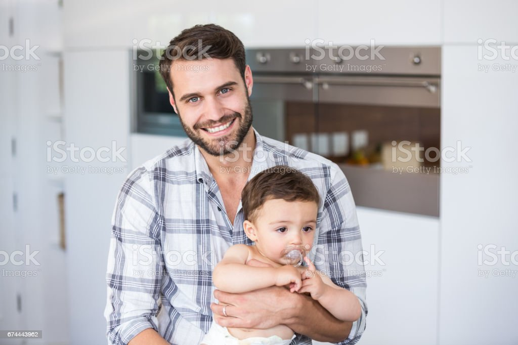 Man smiling while carrying son stock photo