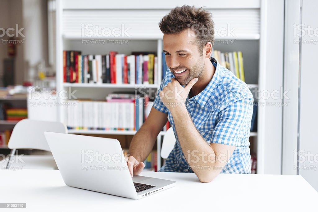 A man smiling while facing his laptop Casual man working on laptop in library Adult Stock Photo