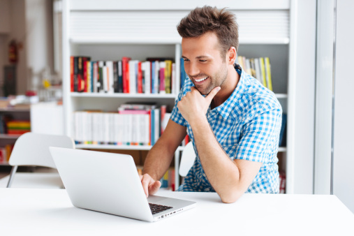 A Man Smiling While Facing His Laptop Stock Photo - Download Image Now