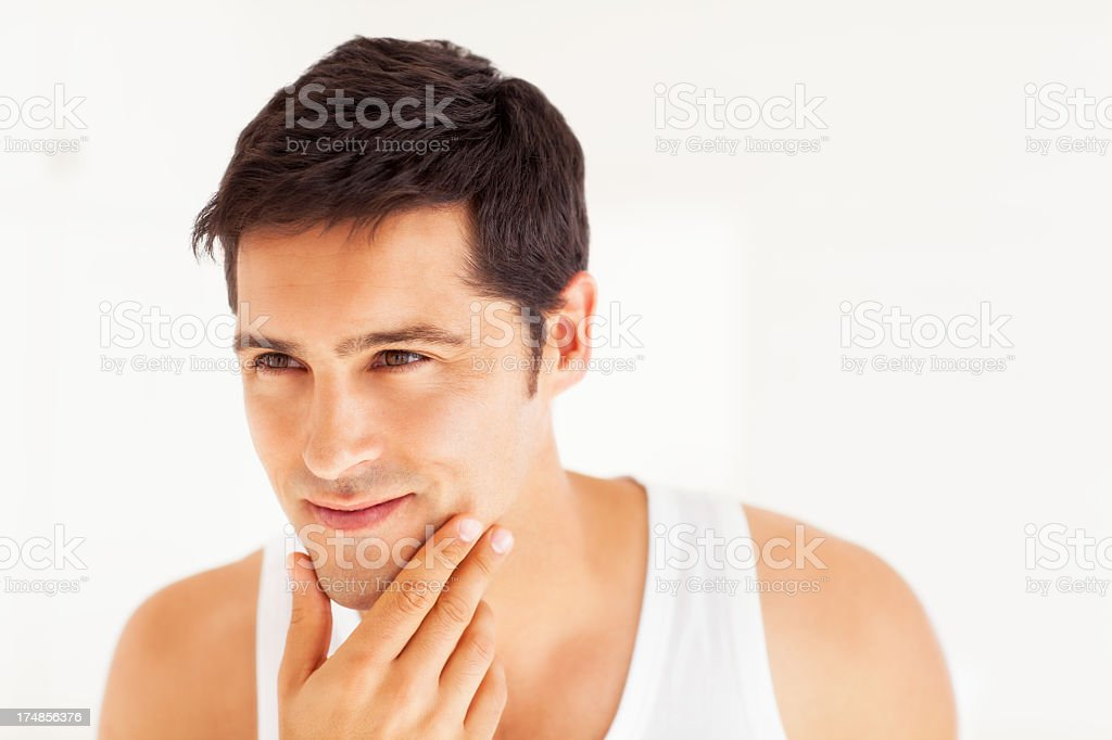 Man smiling with hand on chin as if he has just shaved stock photo