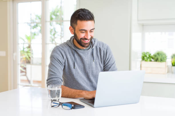 Man smiling working using computer laptop Man smiling working using computer laptop spanish and portuguese ethnicity stock pictures, royalty-free photos & images