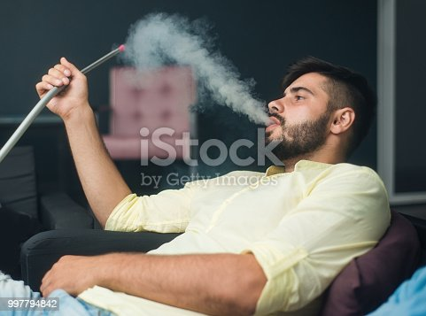 938436312 istock photo Man smokes a hookah, sitting in a bar. Man lets off steam from his mouth 997794842