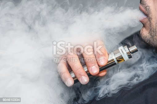 istock A man smokes an electronic cigarette on a gray background, blowing a stream of smoke. Copy space. 934610334