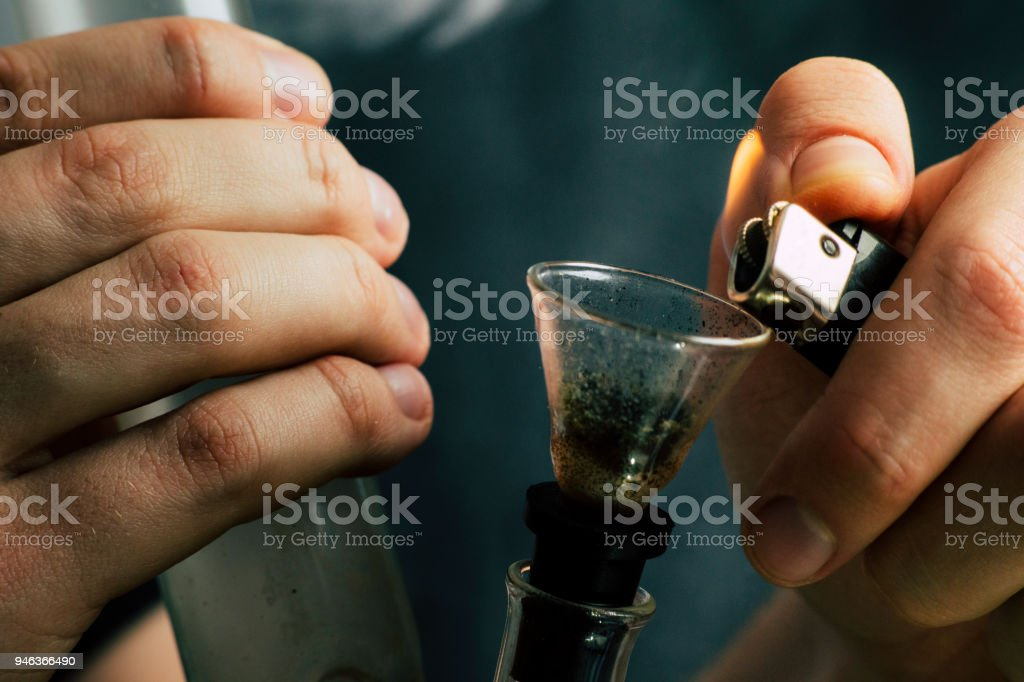A man smokes cannabis weed, a joint and a lighter in his hands. Smoke on a black background. Concepts of medical marijuana use and legalization of the cannabis. stock photo