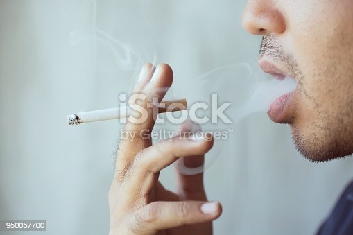 man smoking a cigarette. Cigarette smoke spread.