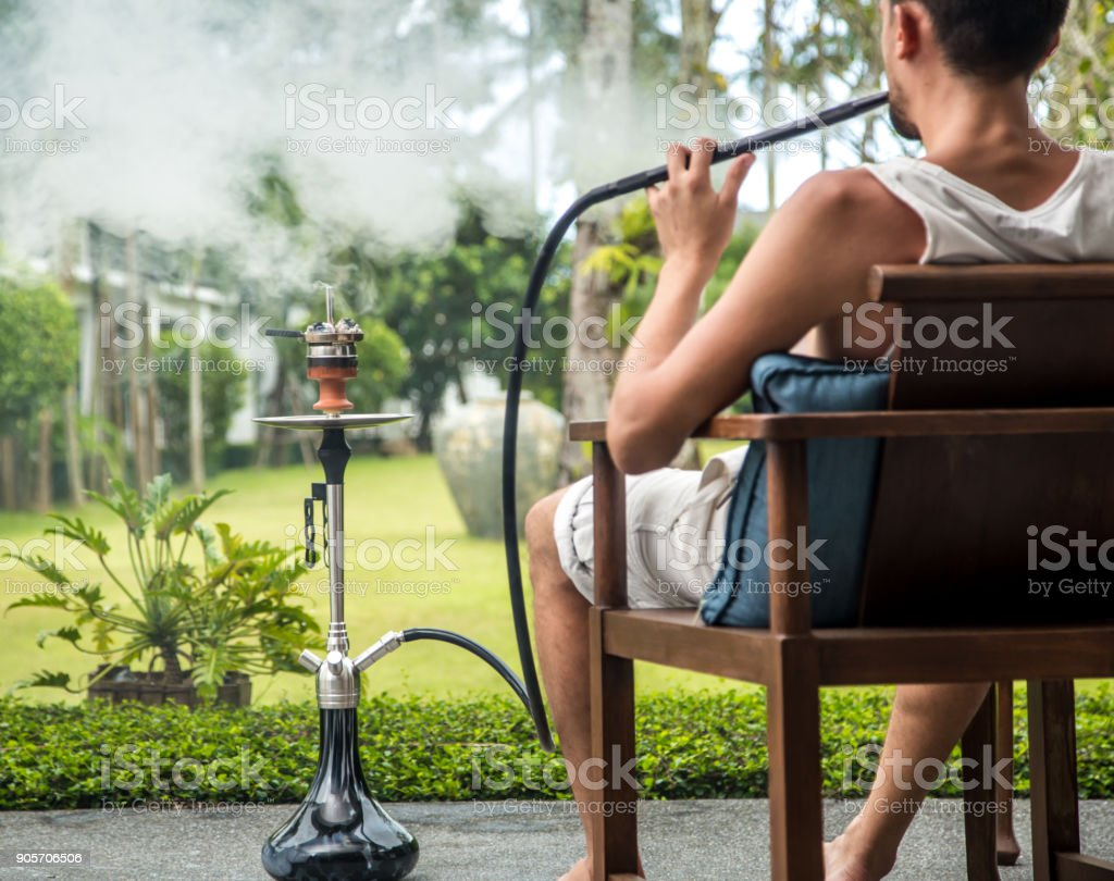 man smoking a hookah on vacation stock photo
