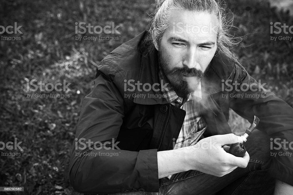 Man smoking a pipe, black and white stock photo