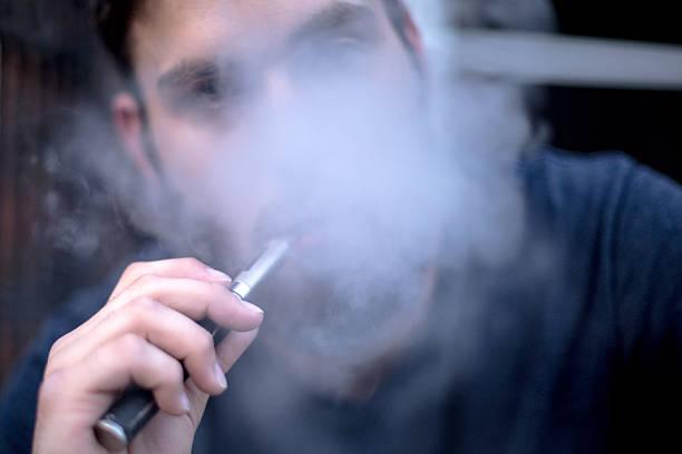 Mann Rauchen und Vaping auf E-cigarette – Foto