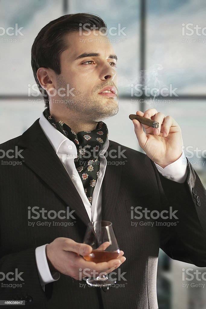 Man smoking cigar and drinking cognac stock photo