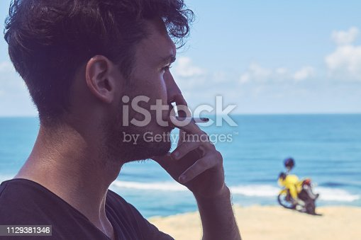 istock Man smoking cigar near motorcycle on the tropical beach. 1129381346