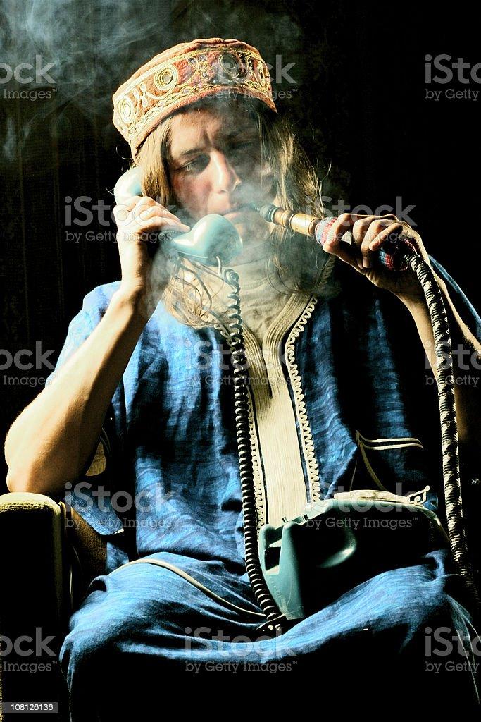Man Smoking Hookah and talking on phone royalty-free stock photo