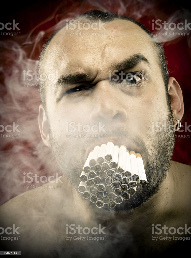 Man Smoking Many Cigarettes in his Mouth royalty-free stock photo