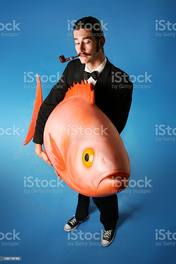Man Smoking Pipe and Carrying Giant Fish stock photo