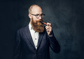 istock A man smoking pipe over grey background. 1074576836