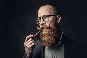 istock A man smoking pipe over grey background. 1074581140