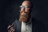 istock A man smoking pipe over grey background. 1074583238