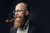 istock A man smoking pipe over grey background. 1074587486
