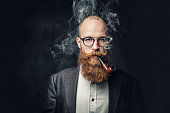 istock A man smoking pipe over grey background. 1074588498