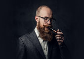 istock A man smoking pipe over grey background. 1074588522